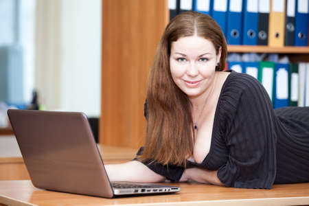Attractive joyful Caucasian woman laying on the desk with laptop photo