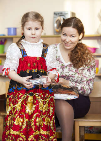 Mother and small daughter in Russian traditional sarafan in kindergarten photo