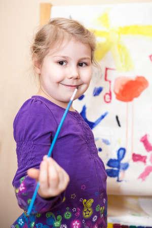 Muchacha preescolar feliz que pinta un cuadro con las pinturas y los cepillos Foto de archivo - 18787789