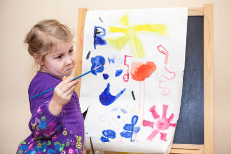 Cute Caucasian girl standing with painting brush near easel photo