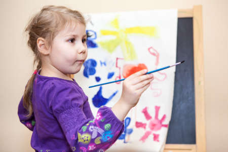 Thoughtful small Caucasian child holding painting brush in hand photo