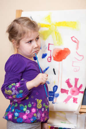 Funny small Caucasian child holding painting brush and thinking about picture photo