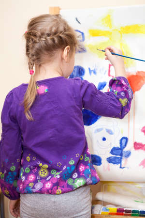 Small Caucasian child painting with brush and paint photo