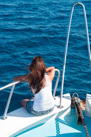 Brunette woman on bow of yacht with legs out photo