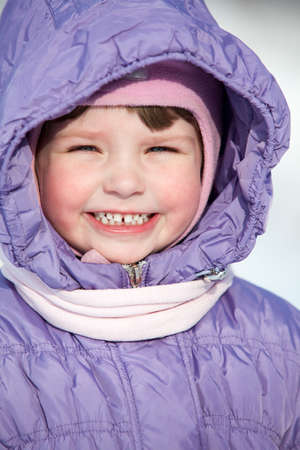 Close-up portrait of small Caucasian girl in winter clothes with hood on head photo