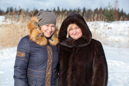 Portrait of two Caucasian cheerful women in warm clothing outdoor photo