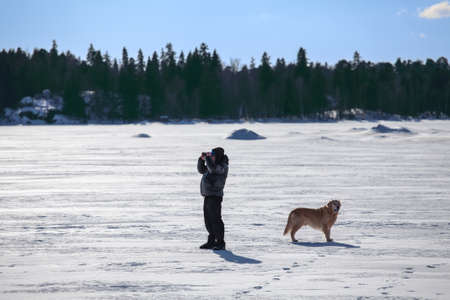 Man with dog looking at binocular and standing on frozen lake photo