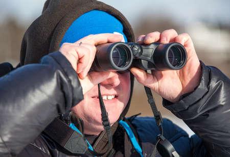 Close up of Caucasian man with binoculars looking far away