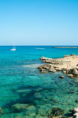 Mediterranean seashore of Cyprus island with rocky coast and white yacht photo