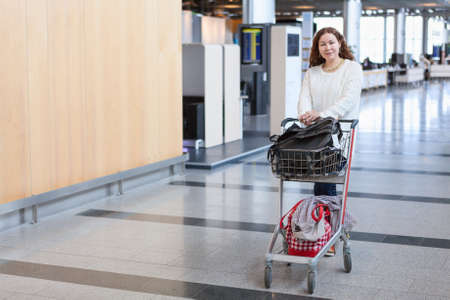 arriving: Young Caucasian woman pulling luggage hand-cart in airport hall