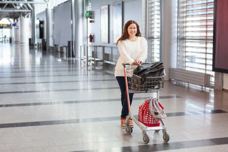 pull along: Young Caucasian woman pulling luggage hand-cart with bags along airport hall  Passenger in waiting area  Stock Photo