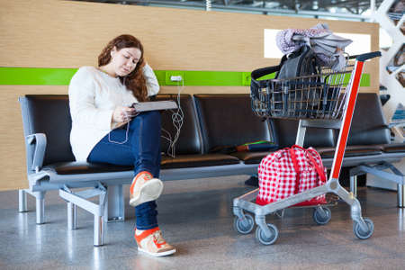 Young Caucasian woman sitting with luggage hand-cart in airport lounge photo