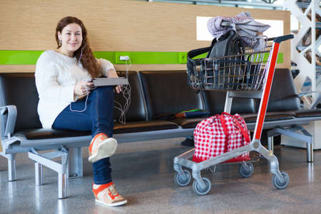 Happy young Caucasian woman sitting with luggage hand-cart in airport lounge photo