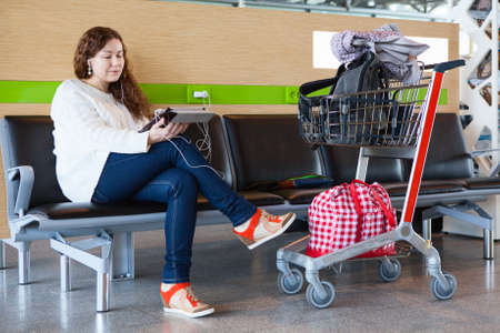 Woman looking at tablet pc in airport lounge with luggage hand-cart photo