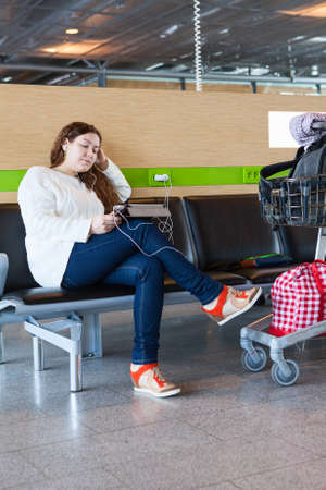 Tired woman looking at tablet pc in airport lounge with luggage hand-cart photo