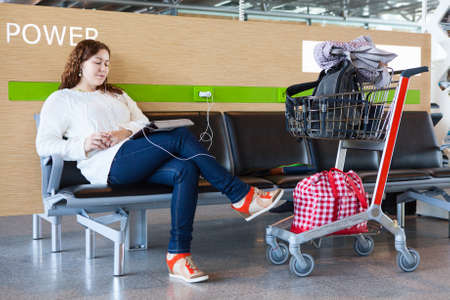 Tired woman charging tablet pc in airport lounge with luggage hand-cart photo