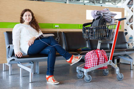 Woman with tablet pc charging devices in airport lounge with luggage hand-cart photo