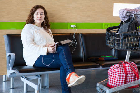Serene woman charging tablet pc in airport lounge with luggage hand-cart photo