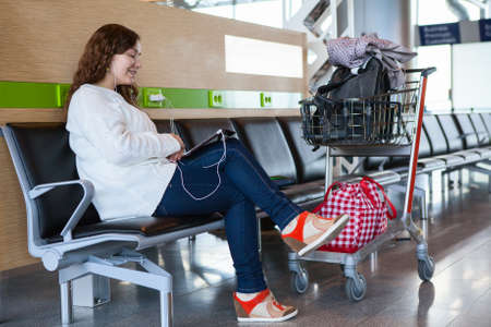 Woman spending time with tablet pc in airport lounge with luggage hand-cart photo