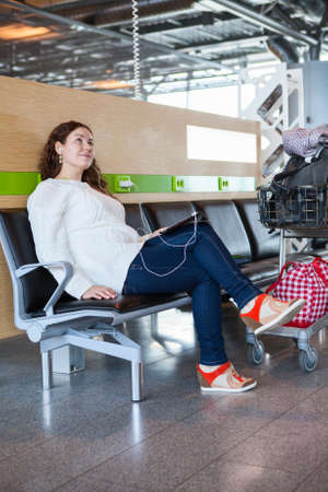Woman dreaming with tablet pc in airport lounge with luggage hand-cart photo