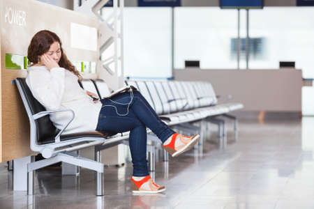 Tired transit passenger sleeping in airport lounge photo