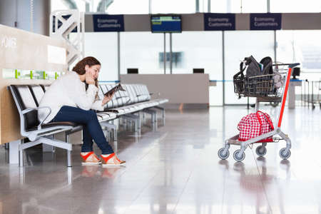 Tired woman waiting flight in airport lounge with luggage hand-cart photo