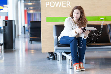 Thoughtful woman with electronic devices near place to charge your phone photo