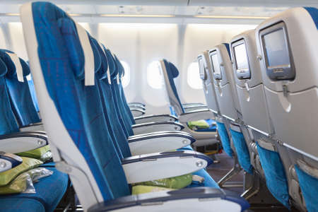 Empty comfortable seats in cabin of huge aircraft with screens in chairs back photo