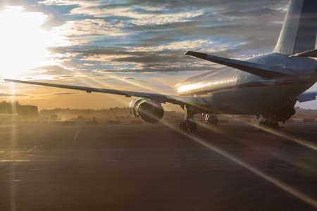 Passenger aircraft standing on runway in sunset sunlights