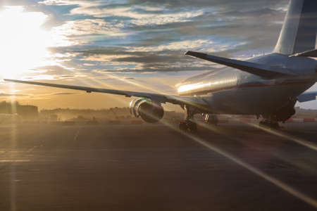 Passenger aircraft standing on runway in sunset sunlights photo