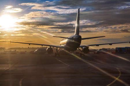 Passagiersvliegtuigen rijden op startbaan in zonsondergang sunlights Stockfoto