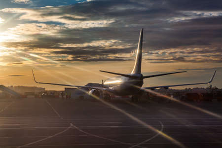 Passenger airliner riding on runway in sunset lights Banque d'images