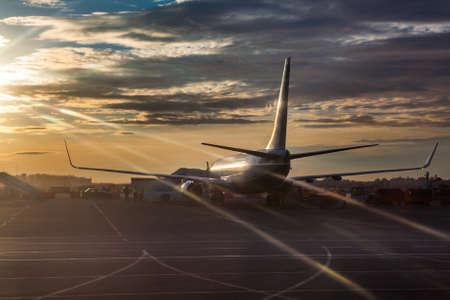 Passenger airliner riding on runway in sunset lights Standard-Bild