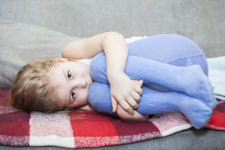 Little Caucasian defenseless child huddled on the couch photo