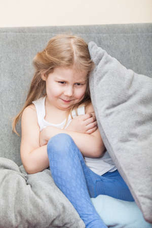 child poverty: Offended Caucasian girl hiding behind a pillow on the couch  Folded her arms Stock Photo