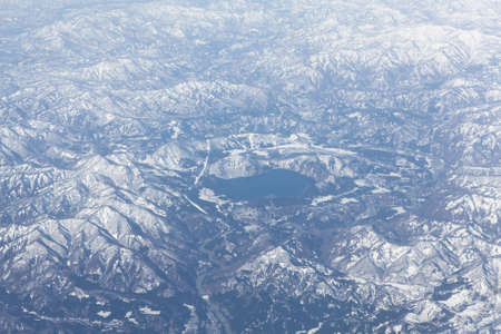 Mountain lake in the middle of snowcovered range, Japan. Aerial view photo