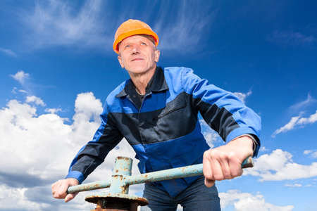 Senior Caucasian worker in a hardhat at the factory with the pipe valve against blue sky photo