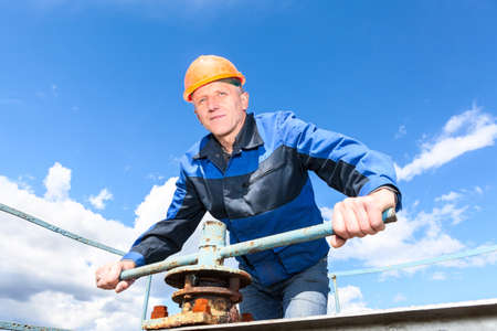 Mature Caucasian worker in a hardhat at the factory with turning the pipe valve photo