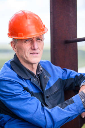 Portrait of an elderly Caucasian man working in a construction helmet photo