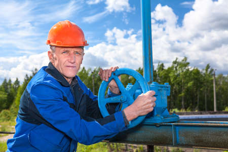 trabajador petrolero: Caucásica trabajador maduro con la vuelta de la válvula