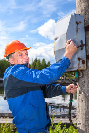 then: Caucasian senior worker with electric shock then turning the power switch Stock Photo