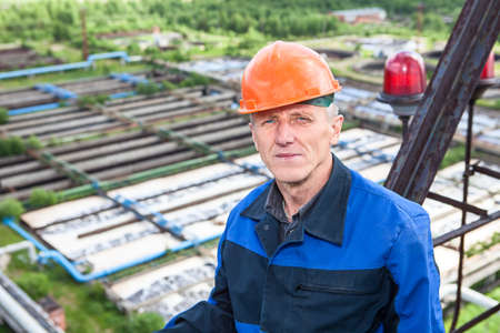 purification: Senior Caucasian manual worker standing against water treatment plant