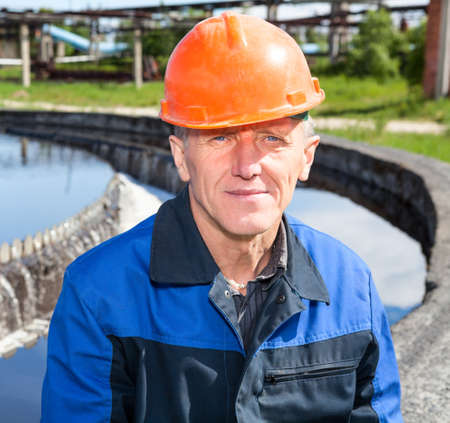 Portrait of Caucasian senior manual worker sitting near water filtration unit photo