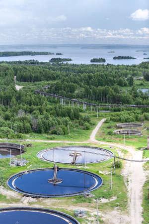 Waterzuiveringsinstallatie in groenblijvende bossen en blauwe meren Stockfoto