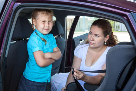 Mother trying to ask a girl get in child safety seat against the wishes Stock Photo - 21305205