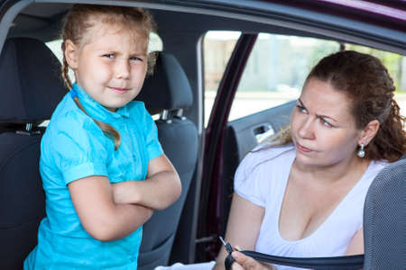 capricious: Mother convincing a girl to get in child safety seat against the wishes