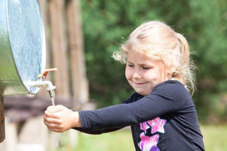Small Caucasian child washing hand in water dispenser outdoor photo
