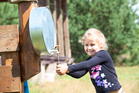 Small Caucasian girl washing hand in water dispenser outdoor photo