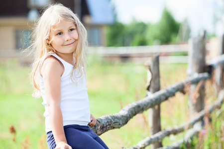 white singlet: Pretty little girl in white singlet sitting on fence. Copyspace Stock Photo