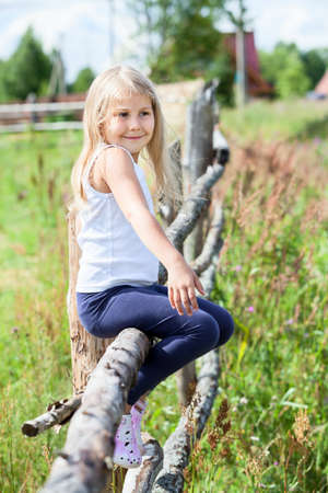 log hair: Beautiful Caucasian girl with blond hair sitting on a log in summer field